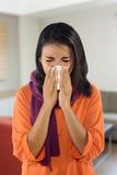 Mujer joven que estornuda Foto de archivo libre de regalías