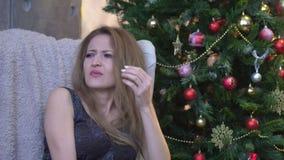 Mujer joven que estornuda en fondo del árbol de navidad almacen de metraje de vídeo