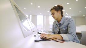 Mujer joven que estudia cerca del ordenador metrajes