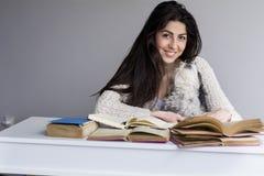 Mujer joven que estudia con los libros para los exámenes con su perro Imagen de archivo libre de regalías