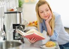 Mujer joven que estudia en cocina Fotos de archivo