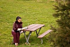 Mujer joven que estudia en el parque con la computadora portátil Imágenes de archivo libres de regalías