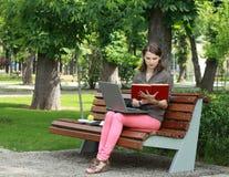 Mujer joven que estudia en un parque Imagen de archivo libre de regalías
