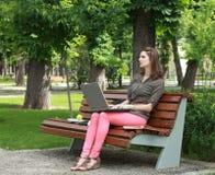 Mujer joven que estudia en un parque imagenes de archivo