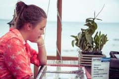 Mujer joven que estudia un menú en un café en la playa mientras que vacaciones con el espacio de la copia Fotografía de archivo libre de regalías
