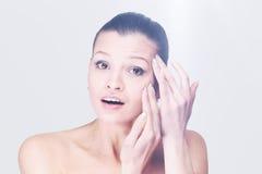 Mujer joven que examina su cara y arrugas que pueden aparecer, ISO Imágenes de archivo libres de regalías