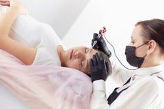 Mujer joven que experimenta el procedimiento del maquillaje permanente de la ceja en sal?n de belleza fotografía de archivo libre de regalías
