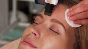 Mujer joven que experimenta el tratamiento facial ultrasónico en el salón de belleza metrajes