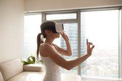 Mujer joven que experimenta los vidrios que llevan de la tecnología de VR, selectin Fotos de archivo