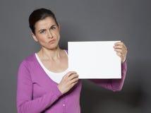 Mujer joven que expresa su mún humor en un tablero blanco Imagen de archivo