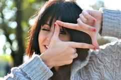 Mujer joven que finge ver el throuhg una lente Foto de archivo libre de regalías