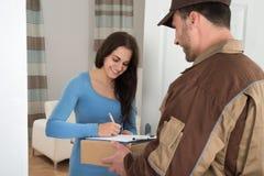 Mujer joven que firma mientras que recibe el mensajero Imagen de archivo libre de regalías