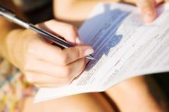 Mujer joven que firma un documento Imagenes de archivo