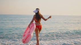 Mujer joven que flota con un buñuelo inflable, lado trasero almacen de video