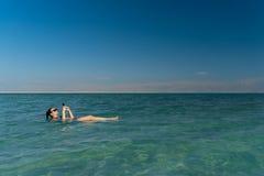 Mujer joven que flota en la superficie del agua del mar muerto y que usa su smartphone foto de archivo libre de regalías