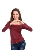 Mujer joven que forma dimensión de una variable del corazón con las manos Imagenes de archivo