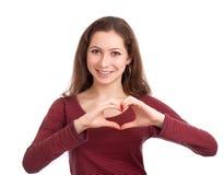 Mujer joven que forma dimensión de una variable del corazón con las manos Imagen de archivo