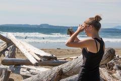 Mujer joven que fotografía el océano con el teléfono móvil Fotos de archivo libres de regalías