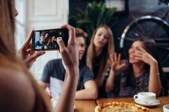 Mujer joven que fotografía a sus amigos positivos en café usando el smartphone, fondo defocused Fotos de archivo