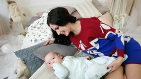 Mujer joven que frota ligeramente, abrazo, acariciando su hijo joven, el retrato de la madre y al bebé, familia en un hogar cómod almacen de metraje de vídeo