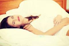 Mujer joven que frota ligeramente su vientre Imagen de archivo libre de regalías