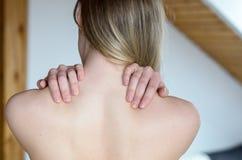 Mujer joven que frota sus hombros desnudos imagen de archivo