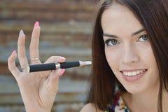 Mujer joven que fuma el cigarrillo electrónico (e-cigarrillo) Fotos de archivo libres de regalías