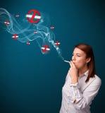 Mujer joven que fuma el cigarrillo peligroso con las muestras de no fumadores Foto de archivo libre de regalías