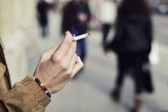 Mujer joven que fuma un cigarrillo Fotografía de archivo libre de regalías