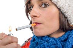 Mujer joven que fuma un cigarrillo, en blanco Imagen de archivo