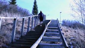 Mujer joven que funciona con para arriba las escaleras de madera