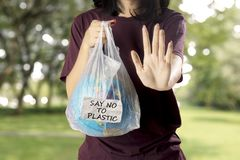 Mujer joven que gesticula para parar la contaminación plástica imagen de archivo