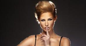Mujer joven que gesticula para reservado o Shushing Imagen de archivo