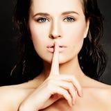 Mujer joven que gesticula para reservado o Shushing Fotografía de archivo