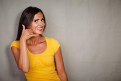 Mujer joven que gesticula una llamada de servicio de atención al cliente Foto de archivo libre de regalías