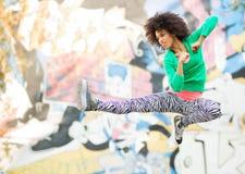 Mujer joven que golpea con el pie en mediados de aire Imagen de archivo libre de regalías