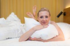 Mujer joven que goza de la cama Fotos de archivo libres de regalías