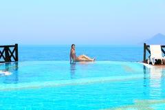 Mujer joven que goza de la piscina de lujo imagen de archivo