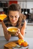 Mujer joven que goza de la sopa de la calabaza en cocina Fotos de archivo libres de regalías