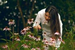 Mujer joven que goza de las flores en el jardín Fotografía de archivo libre de regalías