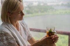 Mujer joven que goza de su té de la mañana, mirando hacia fuera la ventana lluviosa Consumición irreconocible romántica hermosa d fotos de archivo libres de regalías