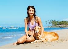 Mujer joven que goza de Sunny Day en la playa con su perro Imagenes de archivo