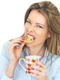 Mujer joven que goza de té y de las galletas fotografía de archivo