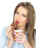 Mujer joven que goza de té y de las galletas Foto de archivo libre de regalías
