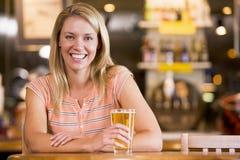 Mujer joven que goza de una cerveza en una barra Fotos de archivo libres de regalías