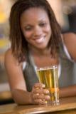 Mujer joven que goza de una cerveza en una barra Imagenes de archivo