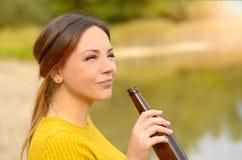 Mujer joven que goza de una cerveza relajante Imagen de archivo libre de regalías