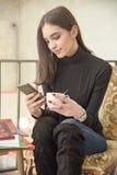 Mujer joven que goza de una taza de café y que habla en su teléfono Imágenes de archivo libres de regalías