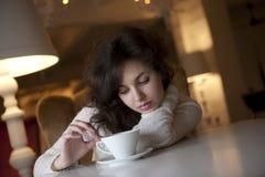 Mujer joven que goza del café del latte en café Fotografía de archivo libre de regalías