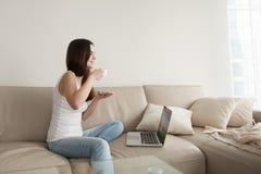 Mujer joven que goza del café en el sofá con el ordenador portátil, día libre Fotografía de archivo